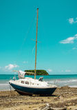 Stranded sail boat on deserted island Stock Photos