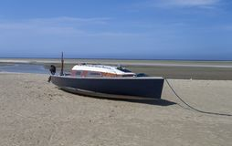 Stranded sailboat in the tideland sea. The photo shows a stranded sailboat in the tideland sea royalty free stock photography