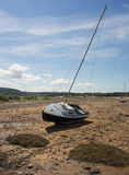 Stranded Sailing Boat. A sailing boat stranded by the receding tide in Red Wharf Bay, Anglesey, Wales Royalty Free Stock Image