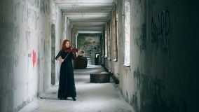 Stranded snowy corridor with a lady playing the violin. 4K stock video