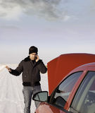 Stranded In Winter. A frustrated young man is calling for help on his cell phone because his car broke down in the winter Stock Images