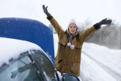 Stranded woman flagging down car in snow Royalty Free Stock Image
