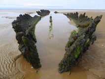 Stranded wreck of a wooden barque. The wreck of the Norwegian sailing barque SS Nornen which sank in March 1897 exposed on the beach at Burnham on Sea, England royalty free stock image