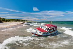 Stranded yacht. Stranded red boat on beach after storm royalty free stock photo