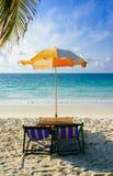 stranden chairs det islan samed paraplyet Arkivbild
