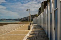 Stranden förlägga i barack på den Yport Habour och strandsidan i Normandie under molnig himmel Arkivfoto