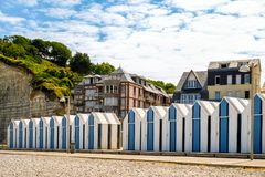 Stranden förlägga i barack på den Yport Habour och strandsidan i Normandie under molnig himmel Royaltyfria Bilder