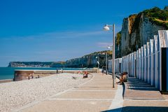 Stranden förlägga i barack på den Yport Habour och strandsidan i Normandie under molnig himmel Royaltyfri Bild