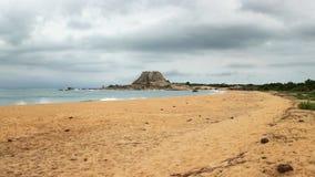 Stranden med den enkla kullen Patanangala vaggar i avstånd på overcas Arkivbild
