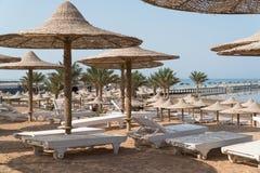 Stranden med paraplyer och solen bäddar ned, som är tomma Royaltyfri Bild