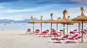 Stranden med sunbeds och slags solskydd av sugrör Fotografering för Bildbyråer