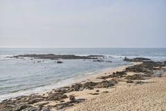 Stranden med vaggar på sand och vatten arkivbild
