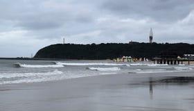 Stranden och guling seglar Arkivfoto