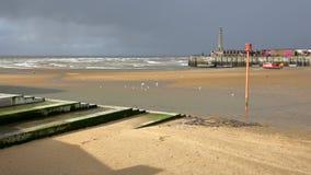 Stranden på lågvatten vid stormigt och blåsväder med den Margate hamnarmen i bakgrunden, Margate, Kent, UK Royaltyfri Foto