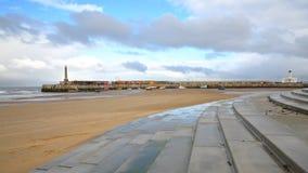 Stranden på lågvatten vid stormigt och blåsväder med den Margate hamnarmen i bakgrunden, Margate, Kent, UK Royaltyfri Fotografi