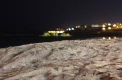 Stranden på natten med stadsljus i avståndet arkivfoto