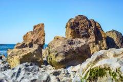 Stranden vaggar bildande, ensliga stenblockstenar som göras av granit Arkivbild