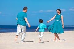 strandfamiljgyckel som har tre tropiska barn Royaltyfri Bild