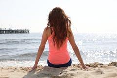 Strandfeiertagsfrau, die Sommersonnesitzen genießt stockfotografie
