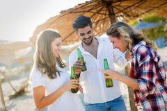 Strandfest mit Freunden Nette junge Leute, die zusammen nette Zeit auf dem Strand verbringen Lizenzfreies Stockbild