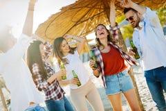 Strandfest mit Freunden Nette junge Leute, die zusammen nette Zeit auf dem Strand verbringen Lizenzfreie Stockfotos