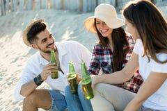 Strandfest mit Freunden Nette junge Leute, die zusammen nette Zeit auf dem Strand verbringen Stockfotos