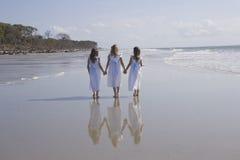 strandflickor tre som går arkivbild