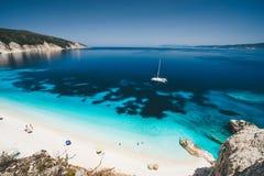 Strandfritidsaktivitet Fteri fjärd, Kefalonia, Grekland Vit katamaranyacht i klart blått havsvatten Turister på sandigt royaltyfria foton