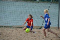 Strandfußball, Mädchen, die in den Teamausstattungen auf dem Sandstrand spielen lizenzfreies stockbild