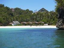 Strandhütten entlang klarem blauem Wasser Stockbild