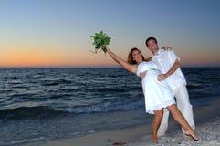 Strandhochzeitspaare feiern Stockfotografie