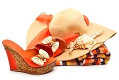 Strandhoed, handdoek, vrouwenschoenen en een zeeschelp stock fotografie