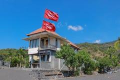 Strandhuis met meerdere verdiepingen met vulkanisch zand Rode vlag met de inschrijving die in de wind fladderen Bergen op de acht royalty-vrije stock afbeelding