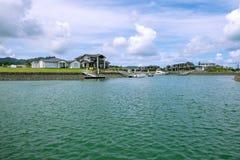 Strandhus med privata fartygbryggor på den Marsden lilla viken, nea Arkivfoton