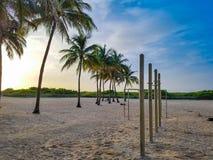 Strandidrottshallen på soluppgång med blå himmel och gömma i handflatan Arkivfoton