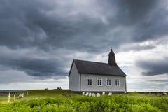 Strandkirkja på Island med mörka moln Fotografering för Bildbyråer