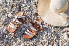 Strandkiselstenar piskar sandal- och för sugrörhatt ferie arkivfoto