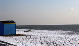 Strandkoja på en snö täckt strand Arkivfoto