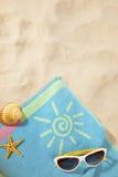 Strandkonzept mit Tuch und Sonnenbrillen Stockfotografie