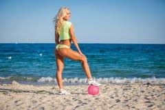 Strandkvinna i bikinin som rymmer en volleyboll Royaltyfri Foto