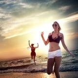 Strandkvinnor som hoppar sommarferie som kyler begrepp Arkivfoto