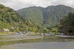 Strandliten vik med bergbakgrund Arkivfoton