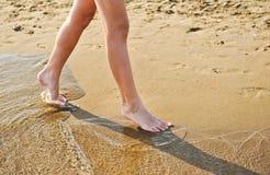 Strandlopp - ung flicka som går på sandstranden som lämnar fotspår i sanden Closeupdetalj av kvinnlig fot och guld- sand Arkivfoto