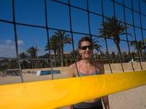 Strandmädchen, das hinter dem Volleyballnetz lächelt Lizenzfreie Stockfotos