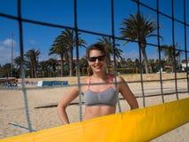 Strandmädchen, das hinter dem Volleyballnetz lächelt Stockfoto
