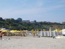 Strandmening met toeristen het looien en paraplu's Royalty-vrije Stock Afbeeldingen