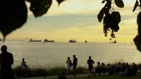 Strandmensen met schepen in ver stock video