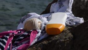 Strandobjekt - swimwear, solskyddskräm och ett skal på en kust vaggar stock video