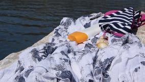 Strandobjekt - swimwear, solskyddskräm och ett skal på en kust vaggar lager videofilmer