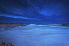 strandoklarheter över sandig stormskymning Royaltyfri Bild